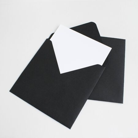 Two black envelopes with white paper on grey background. Postcard template.