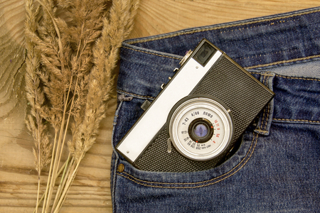 warm and romantic autumn - jeans, an old retro camera, leaves and plants