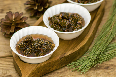 tasty jam made from young spruce cones in white cups Foto de archivo