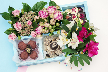 handmade chocolates decorated in a wooden box with beautiful fresh flowers bouquet