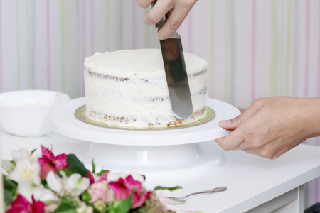 The confectioner's hands decorate the cake with a white tasty cream