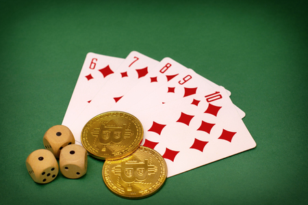 objects of a poker game - game cards, game dice and gold bitcoins on a green background