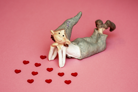 loving boy elf ceramic with hearts on coral background. Banque d'images