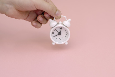 small round white clock alarm clock keeps baby's hand on pink background.