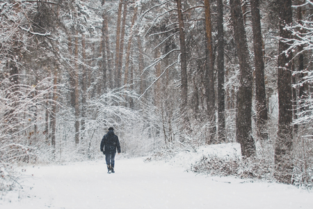 in a snowy forest lonely figure of a man on a walk