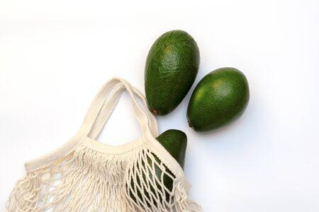Avocado in a string bag on a white background.zero waste
