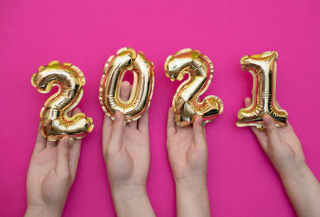 Golden new year numbers-balls 2021 held by people at arms length up on a pink background.