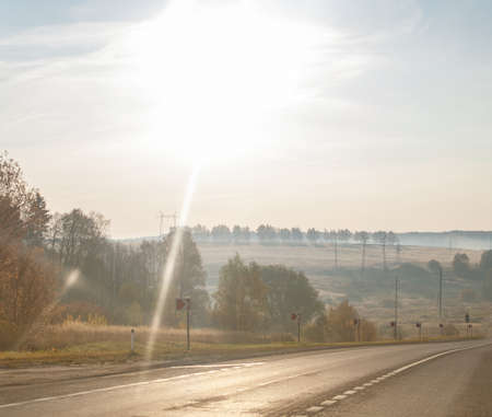 Autumn morning road with bright shining sun. Travel by car.