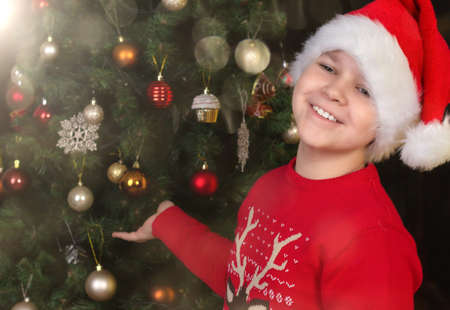 A happy child in a Santa Claus hat with a happy smile near the Christmas tree.