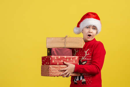 A surprised emotional child in a Santa Claus hat holds Packed Christmas gift boxes on a yellow background in the Studio. Copy space.