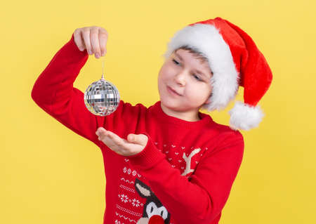 A beautiful 10-year-old boy in a Santa Claus hat holds a Christmas disco ball on a yellow background. Isolate.