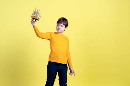 A 9-year-old boy plays with a handmade toy boat and imagines himself as a captain and a traveler on a yellow background in the Studio.