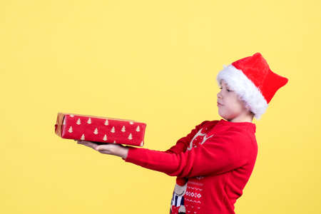 A surprised emotional child in a Santa hat holds a Packed Christmas gift box on a yellow background in the Studio. Copy space.