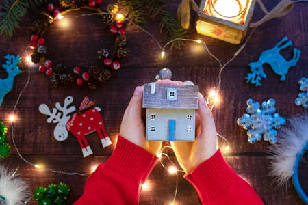 Christmas composition. The hands of a child in a red sweater hold a Christmas cozy wooden Scandinavian house. Stock fotó