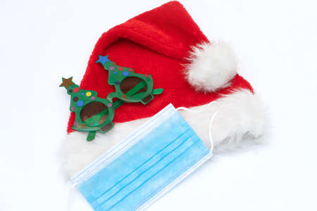Coronavirus Christmas Santa hat and medical mask with festive new year glasses on white background. The concept of self-isolation and celebrating the new year during the pandemic.