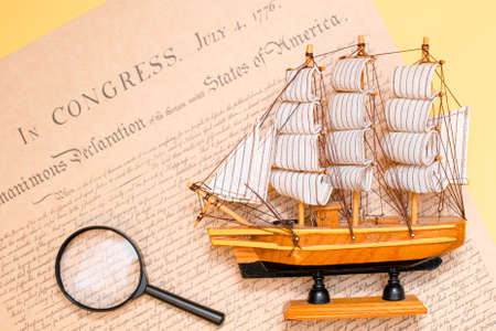 Ship made of wood and fabric handmade on the background of an excerpt from a copy of the document of 1776 on the signing of the independence of America. Stock fotó