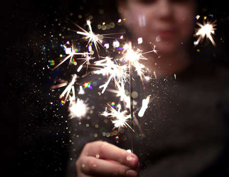 Christmas party. A child holds a lit firework on a shiny background with bright gold Christmas lights. Dark concept. Stock fotó
