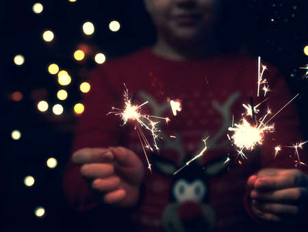 Christmas party. A child holds a lit firework on a shiny background with bright gold Christmas lights. New years eve. Dark concept.