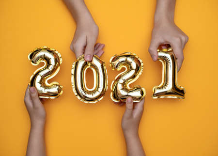 Golden new year numbers-balls 2021 held by people at arms length up on a yellow background.