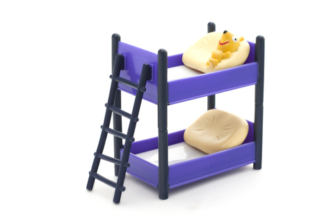Doll bunk bed with stairs and pillows on a white background Stock Photo