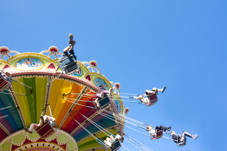 carnival ride: Colorful chain swing carousel in motion at amusement park on blue sky background