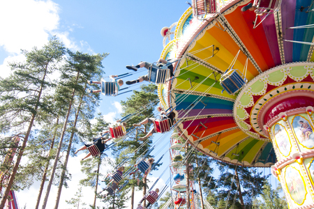 chain swing ride: Colorful chain swing carousel in motion at amusement park on blue sky background