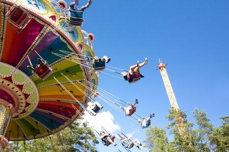 Carrusel colorido de la oscilación de la cadena en el movimiento en el parque de atracciones en fondo del cielo azul