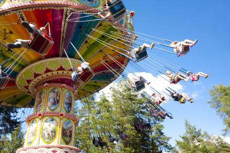 De kleurrijke carrousel van de kettingsschommeling in motie bij pretpark op blauwe hemelachtergrond Stockfoto