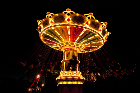 chain swing ride: Colorful chain swing carousel in motion at amusement park at night