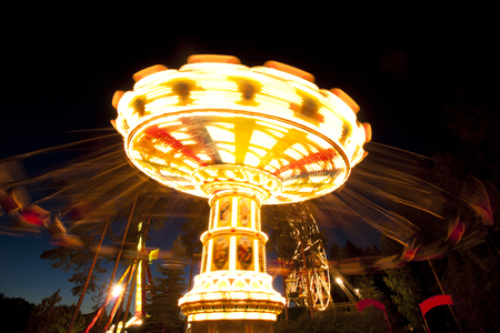 Colorful chain swing carousel in motion at amusement park at night