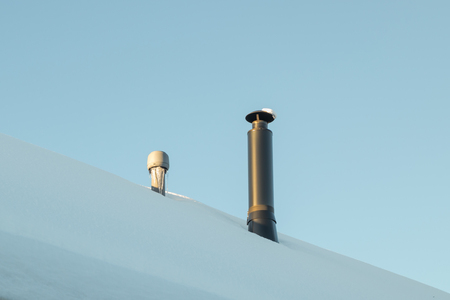 Two chimneys on the snow-covered roof. Standard-Bild - 116904757