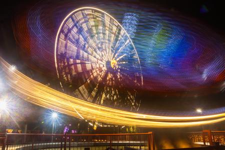 Ferris wheel in motion at the amusement park, night illumination. Long exposure.