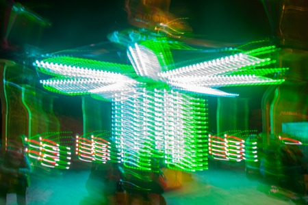 A blurry colorful carousel in motion at the amusement park, night illumination. The effect of bokeh and long exposure