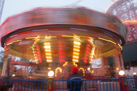 A blurry colorful carousel in motion at the amusement park, evening illumination. The effect of bokeh and long exposure Stockfoto