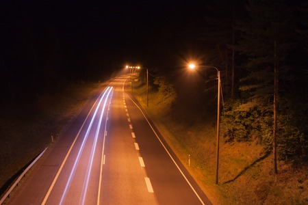 Long exposure photo of traffic with blurred traces from cars at night in Finland, top view.