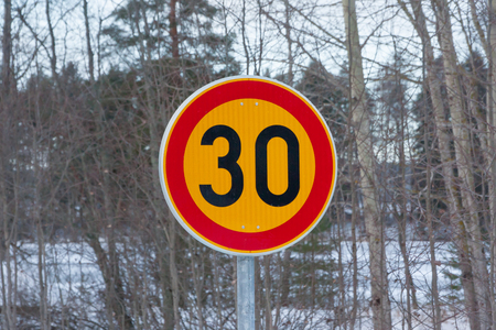 Speed limit 30 kilometers per hour road sign on trees background at winter in Finland. Stock Photo