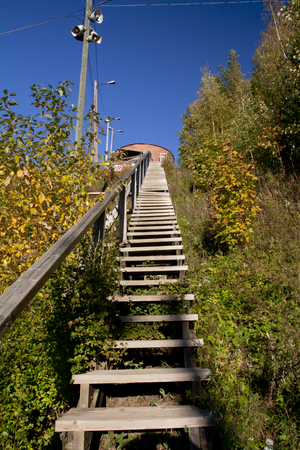 Long wood stairs up to top of bush-covered hill. Imagens