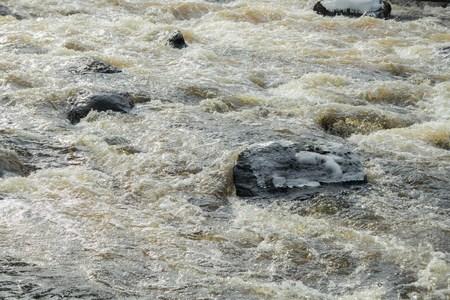 Rough river Jokelanjoki and stones in water, Kouvola, Finland.