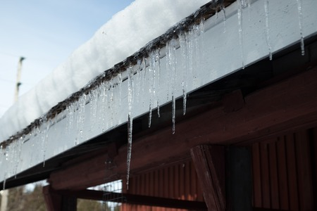 Sharp icicles and melted snow hanging from eaves of roof. Beautiful transparent icicles slowly gliding of a roof. Stok Fotoğraf