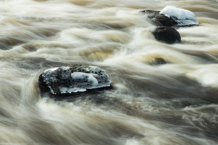 Long exposure photo. Rough river Jokelanjoki and stones in water, Kouvola, Finland.