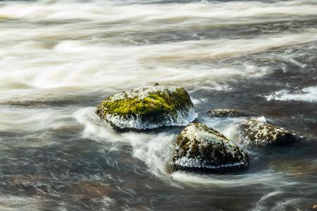 Long exposure photo. Rough river Jokelanjoki and stones in water, Kouvola, Finland.