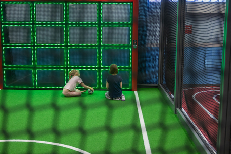 Blurred children are playing behind the net at indoor playground in activity park.