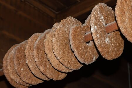 Rye bread drying on a pole. Traditional way to store bread in an farmhouse, hanging from a pole in the ceiling