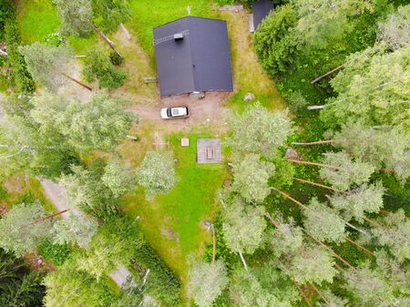 Aerial view of wooden cottage in green forest at rural summer in Finland
