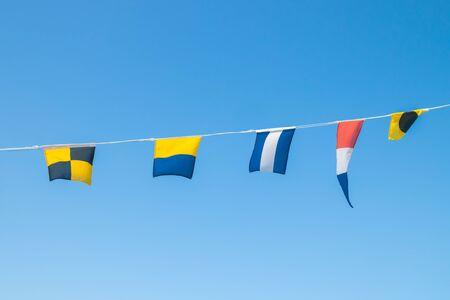 Nautical flags on the ship against blue sky