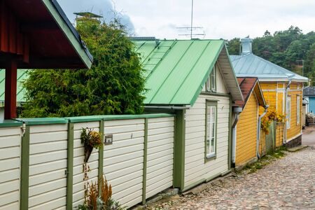 Narrow street of Old Porvoo, Finland. Beautiful city autumn landscape with colorful wooden buildings.