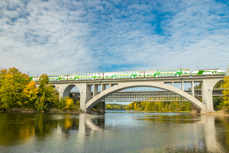 Kouvola, Finland - 25 September, 2019: Autumn landscape of bridge with moving passenger train and Kymijoki river waters in Finland, Kymenlaakso, Kouvola, Koria