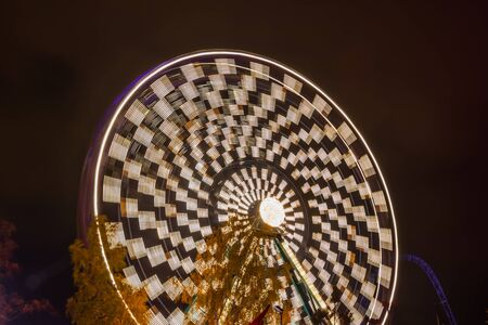 Ferris wheel in motion at the amusement park, night illumination. Long exposure.