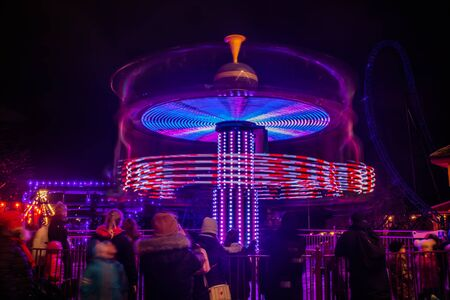 A blurry colorful carousel in motion at the amusement park, night illumination. Long exposure. Stock fotó