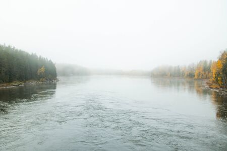 Beautiful autumn landscape of Kymijoki river waters in fog. Finland, Kymenlaakso, Kotka